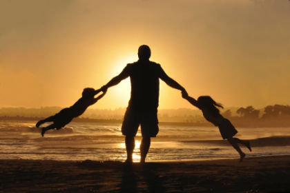 father and children on beach at sunset